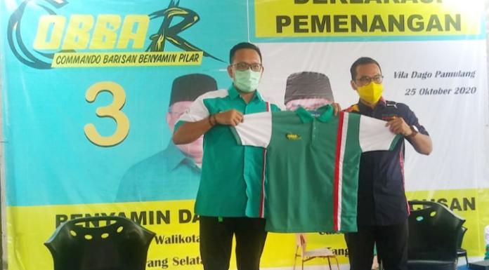 Adikara (Presiden REMUV) menyerahkan baju 'COBBAR' kepada calon wakil walikota Pilar Saga Ichsan.(Foto/JKW)